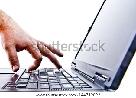 Silhouetted image someone typing on laptop computer Symbol shadow economy illegal operations cracking computer passwords fraud hacking advertising sales illegal non payment taxes concealment income