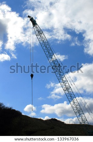 Silhouetted industrial crane with cloudscape background.