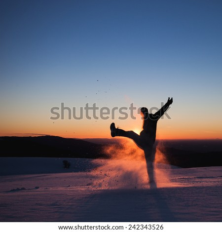 silhouetted man kicking snow in winter landscape  - stock photo