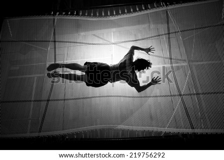 silhouetted man landing with stomach on trampoline