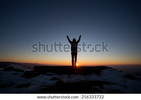 silhouetted man standing on mountain in sunset