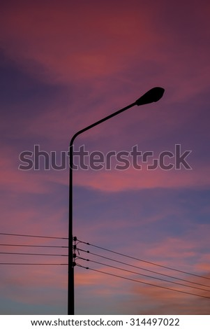 Silhouetted of the electricity transmission pylon with the beautiful sunset background