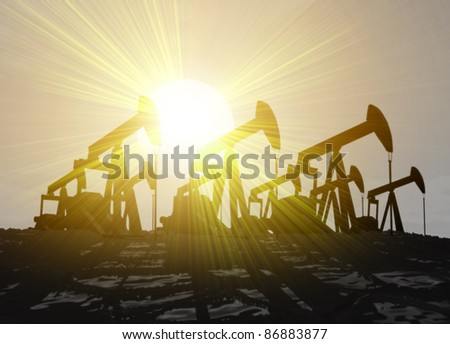 Silhouetted oil wells set against evening sky with the sun flaring from behind - stock photo