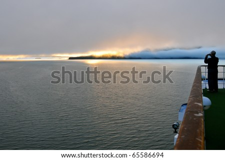 silhouetted passenger photographs dramatic alaskan sunrise from cruise ship deck as travel background - stock photo