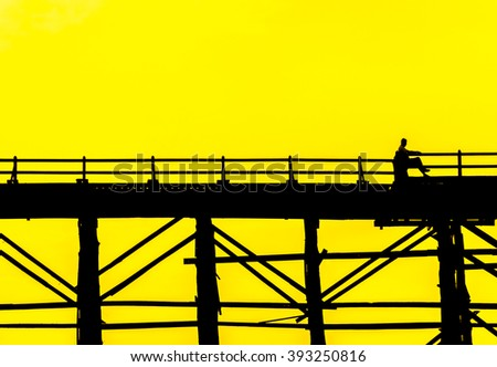 Silhouetted person sitting on the chair in bridge at sunset, Sangkla, Kanjanaburi Province, Thailand