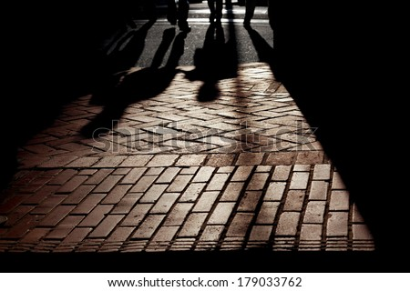 Silhouetted shadows of people walking on brick pavement, strongly backlit, stylized. - stock photo