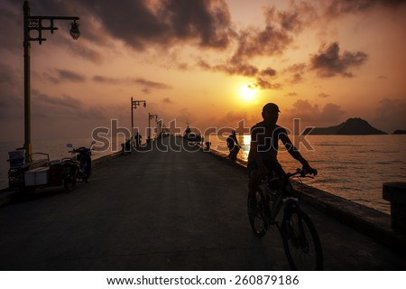 Silhouetted unidentified man riding a bike on jetty at Ao Manao bay in Prachuap Khiri Khan, Thailand - stock photo