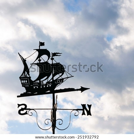 Silhouetted View of an Antique Ship Weather Vane against a Stormy Sky