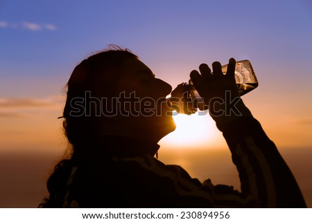 Silhouetted woman drinking water from a bottle at sunset - stock photo