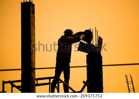 Silhouettes Construction workers,labor working on a construction site  - stock photo