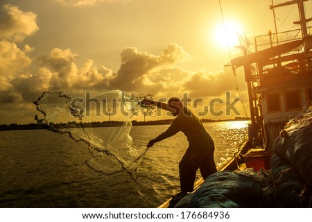 Silhouettes fisherman casting on a crab boat. - stock photo