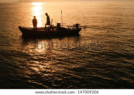 Silhouettes fishing boats and fisherman in the sea after sunset
