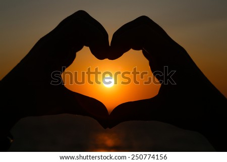 Silhouettes hand heart shaped with sun sets and the sky orange - stock photo