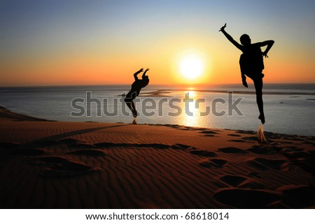 silhouettes jumping on beach in sunset for fun - stock photo