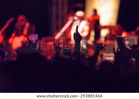 silhouettes of a crowd of cheering fans during a live concert - stock photo