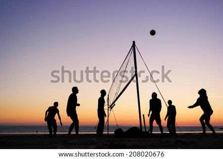 Silhouettes of a group of young people playing beach volleyball on the beach in Brittany, France  - stock photo