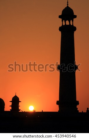 Silhouettes of a tower of Taj Mahal during the evening