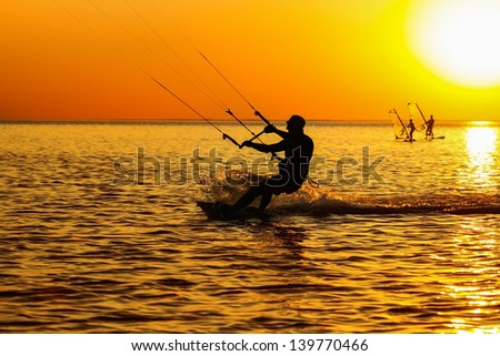 Silhouettes of a windsurfers sailing in the sea at sunset  - stock photo