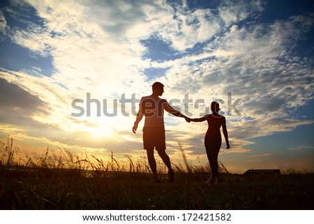 Silhouettes of a young couple lovers at sunset in rays of setting sun - stock photo