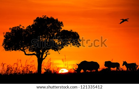 Silhouettes of African animals against the sunset - stock photo