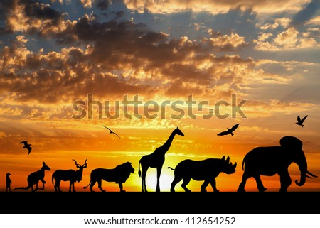 Silhouettes of animals on golden cloudy sunset background - stock photo