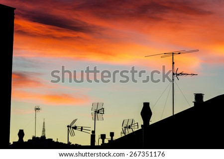Silhouettes of antennas and chimneys backlit at sunset with colorful sky clouds - stock photo