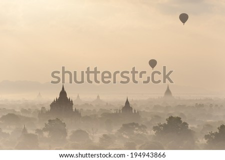 Silhouettes of balloons and ancient Sulamani and Tha Beik Hmauk Gu Hpaya at amazing sunrise. Architecture of old Buddhist Temples at Bagan Kingdom, Myanmar (Burma). Travel landscapes and destinations - stock photo