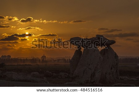 Silhouettes of Big Stones on orange sunset's cloudscape background.Far from city's silhuettes