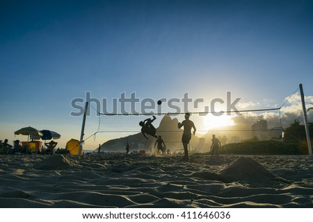 Silhouettes of Brazilians playing futevolei (footvolley) against a sunset backdrop of Dois Irmaos Two Brothers Mountain on Ipanema Beach, Rio de Janeiro Brazil  - stock photo