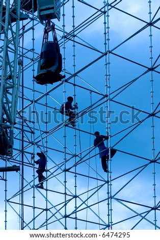 Silhouettes of builders on a background of the sky - stock photo
