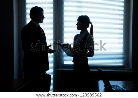 silhouettes of business partners talking against the window in the office - stock photo