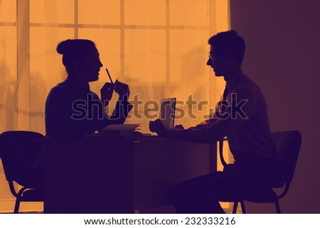 Silhouettes of business people on orange sunset. Negotiations. Relations in the team of employees of one company. To know the truth about the situation on the market. - stock photo