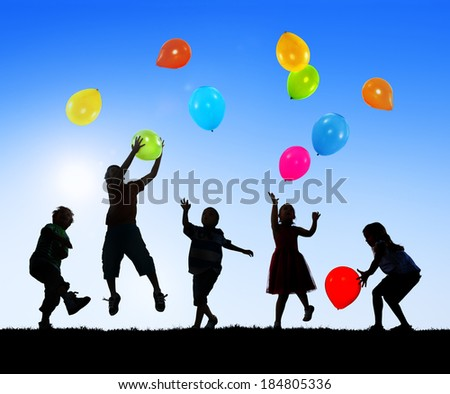 Silhouettes of Cheerful Children Playing Balloons Outdoors - stock photo