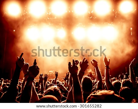 silhouettes of concert crowd in front of bright stage lights - a small DOF signifies that the focused area is narrow - stock photo