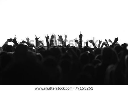 silhouettes of concert crowd in front of bright stage lights, black and white version - stock photo
