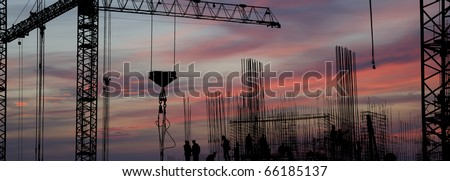 silhouettes of construction workers, construction equipment and elements of a building under construction at Sunset - stock photo