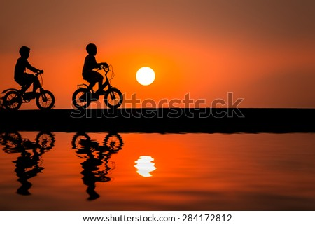 Silhouettes of couple child on bicycle against sunset sky  - stock photo