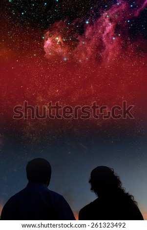 Silhouettes of couple looking at stars. Starry night sky with colorful galaxies, astronomical background with place for your text.Elements of this image furnished by NASA. - stock photo