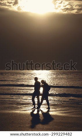 Silhouettes of couple walking along a beach at dramatic sunset and talking. Crisis in relations background. - stock photo