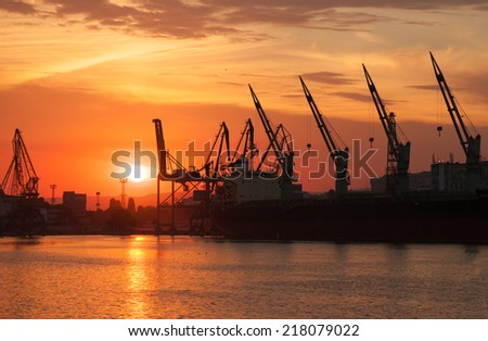 Silhouettes of cranes and industrial cargo ships in Varna port at sunset - stock photo