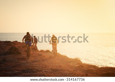 Silhouettes of cyclists on the beach - stock photo