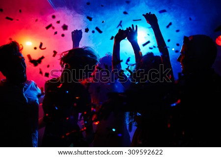 Silhouettes of dancers moving in confetti - stock photo