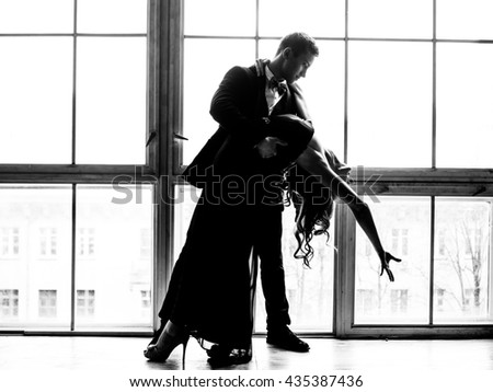 silhouettes of dancing couples against the background of a window