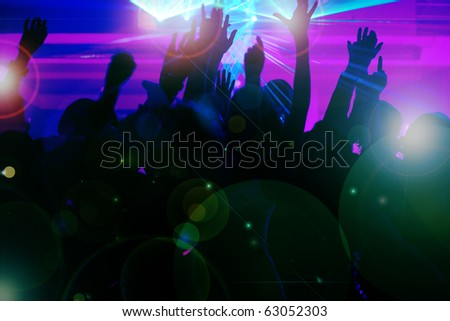 Silhouettes of dancing people having a celebration in a disco club, the light show is sending laser beams through the backlit scene - beware: very psychedelic forms and colors - stock photo