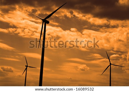 Silhouettes of eolian turbines against a cloudy sky.