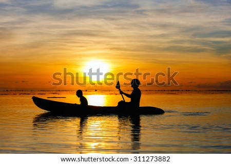 Silhouettes of family of father and daughter paddling at tropical ocean at sunset - stock photo