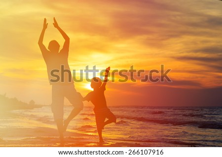 silhouettes of father and son doing yoga at sunset sea - stock photo
