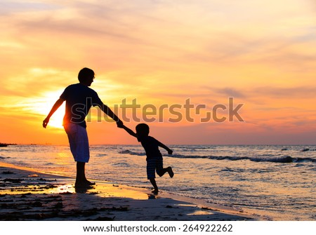 silhouettes of father and son having fun on sunset beach - stock photo