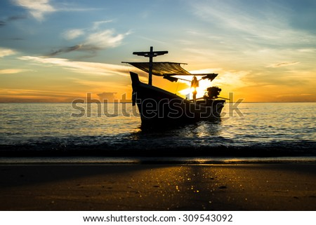 Silhouettes of Fishing boat on the beach.