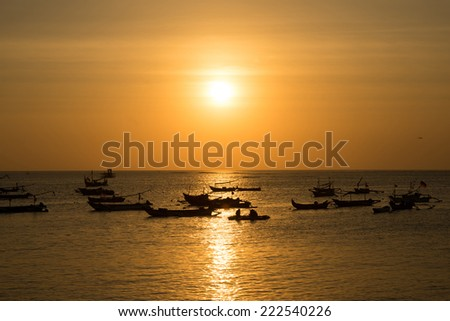 silhouettes of fishing boats at sunset in Bali. - stock photo